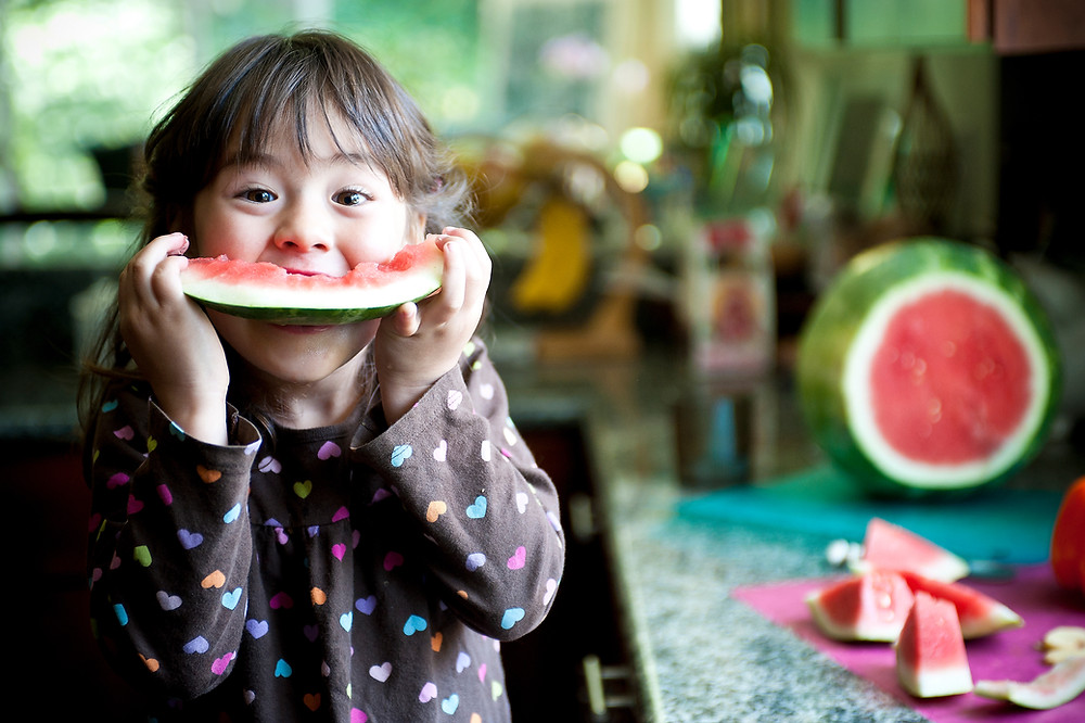 Young girl eating large piece of watermelon