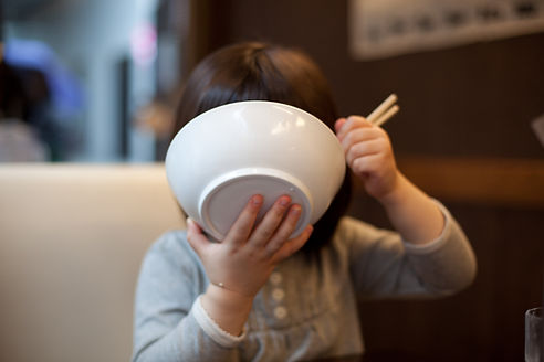 ご飯をかきこむ子供