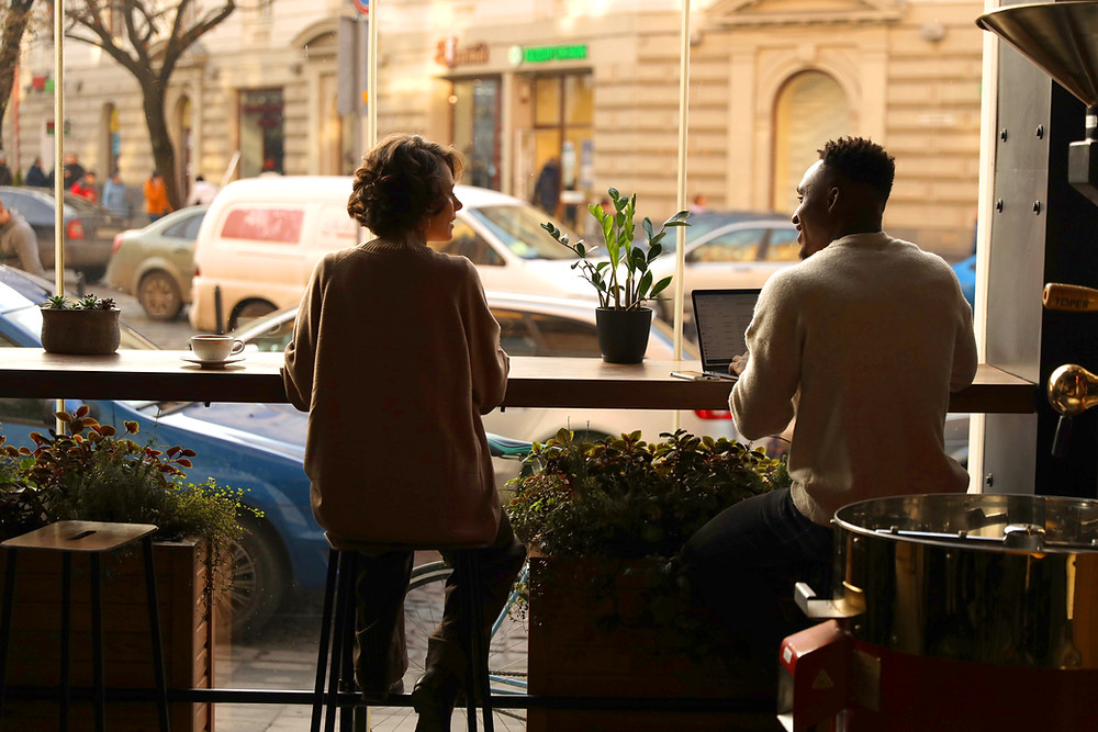 This is a picture of two young adults sitting next to each other at a café, a man and a woman. They're both sitting at a bar next to a large glass window. The man is sitting in front of a laptop, and the man and woman are looking at each other. There are plants on the table. Outside, there are cars, tan buildings, and a tree.