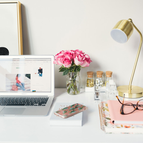 Desk with computer and flowers.