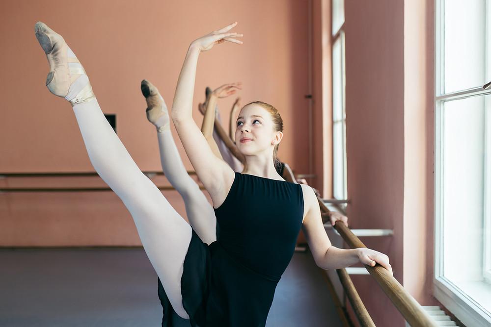 Ballet dancers extending their legs at the ballet barre.