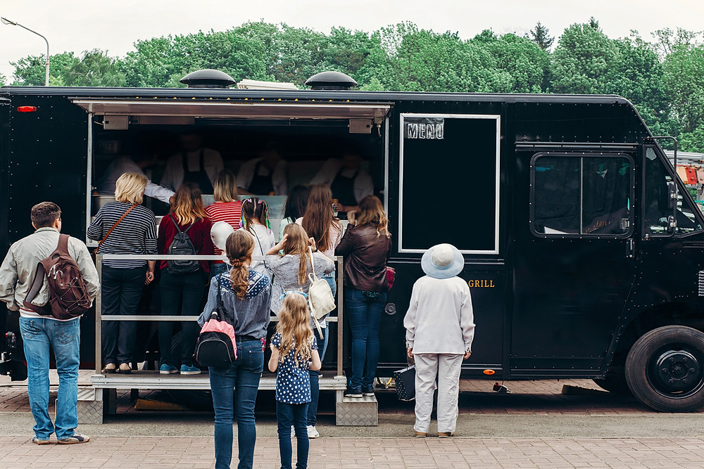 People waiting in line at a food truck.