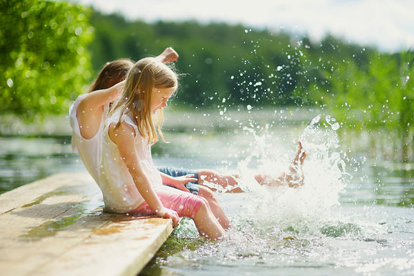 Two Kids Splashing Water From Dock