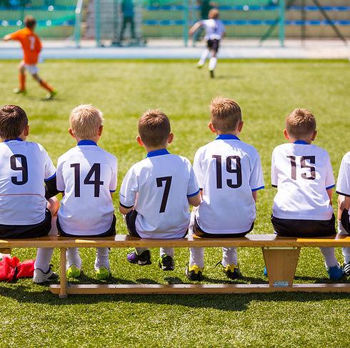 Unga fotbollsspelare på bänken