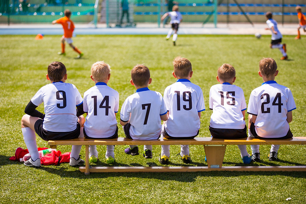 Kids watching football on a bench