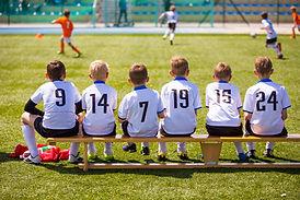 Mladí fotbalisté na lavičce