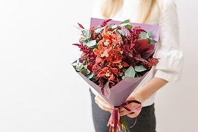 オレンジ色の蘭と他の花のブーケを持つ少女