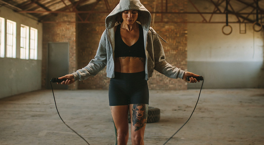 What Are The 5 Best Exercises? Skipping. A woman is skipping in a boxing gym.