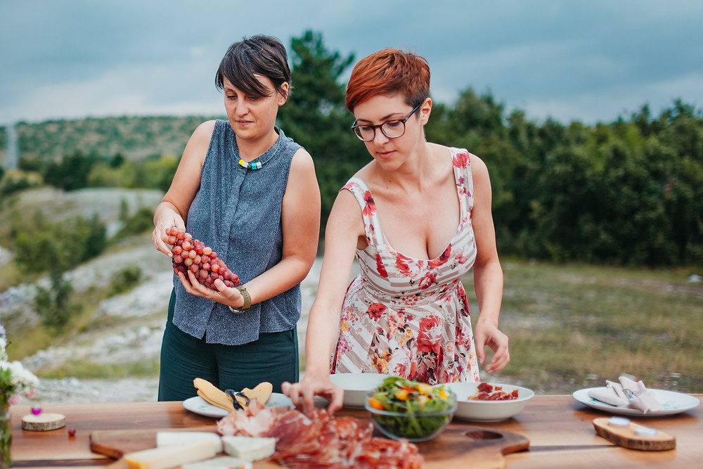 Two women putting food on a picnic table