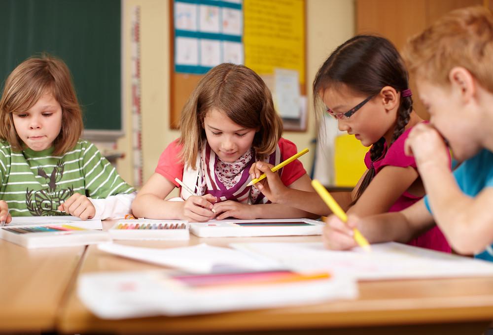 4 Enfants attablés sont concentrés sur un travail scolaire