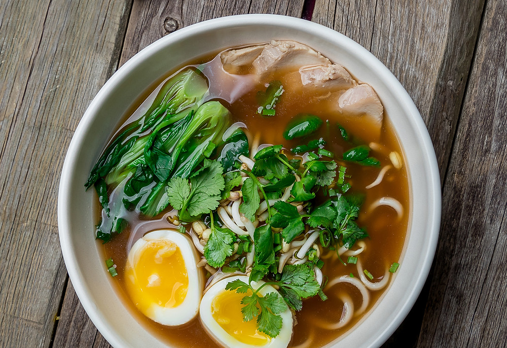 Nourishing bowl of noodles, eggs, vegetables and broth for postnatal nutrition recovery