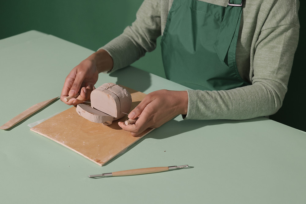 Artist in an apron (cannot see face) cutting clay block with wire