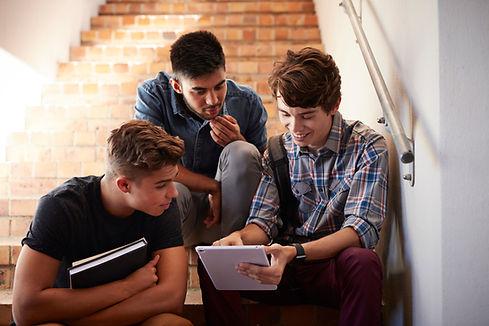 Uczniowie siedzą na schodach