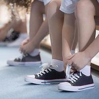 Kinder, die ihre Schuhe binden