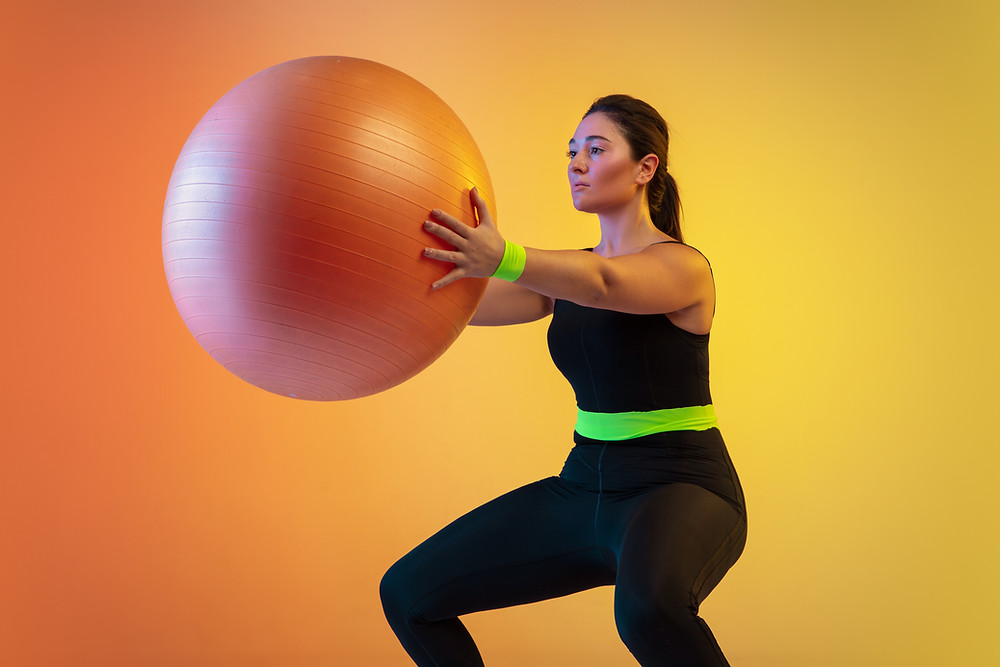 women working out with exercise ball yellow background