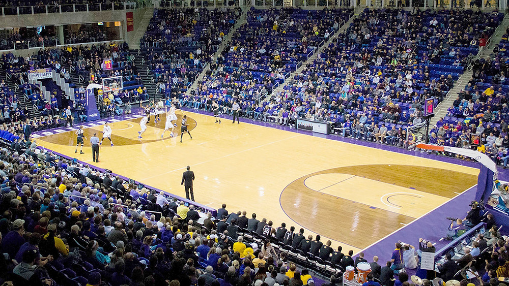 Wide shot of basketball court during game and crowd in seats.