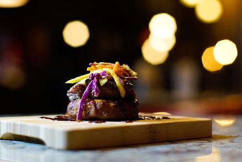 Un morceaux de viande sur une planche en bois accompagné par de la sauce et sur le dessus des morceaux de légumes jaunes et violets