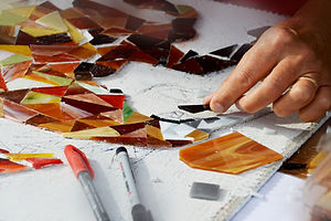 hands working on mosaic tiles, situating on a sketch