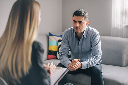 Man sitting on a couch engaging in a therapy session.