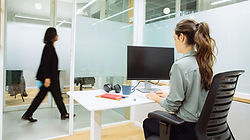 Modern Office with a ladying walking and a staff member sitting at the desk at the computer