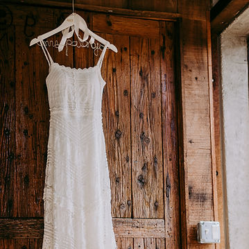 A white wedding dress on a hanger, hung up on the outside of a wardrobe.