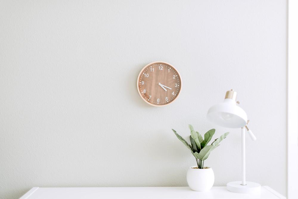 Une horloge au mur indique que le temps passe, la plante inspire la vie