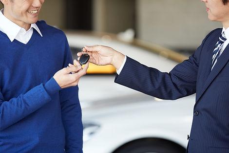 自動車ディーラーで鍵を受け取る男性