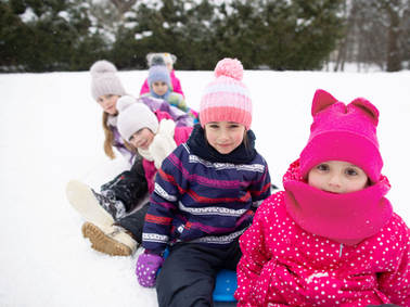 Children Sledding in Snow