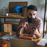 Ein Mann bucht mit seinem Smartphone einen einen Schnupperkurs in einer Sprache.