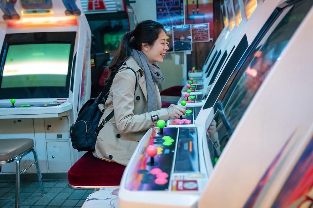 Woman sitting at an arcade game smiling