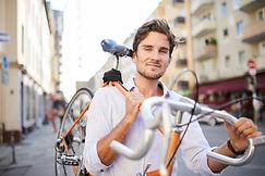 Mann trägt Fahrrad