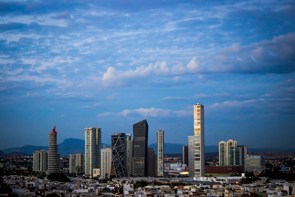 City skyline with blue skies and white clouds, with tall sky scraper buildings and surrounding houses beneath.