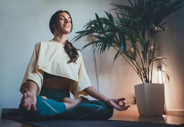 Woman meditating and envisioning at home, happy and content in seated position