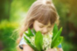 Petite fille avec un bouquet de muguet