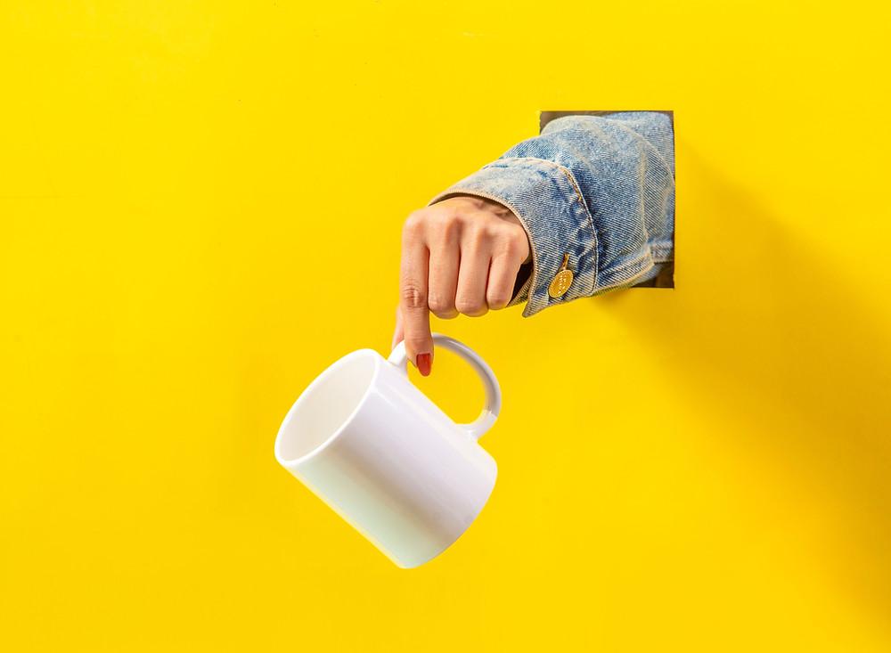 A hand holding a glossy white mug