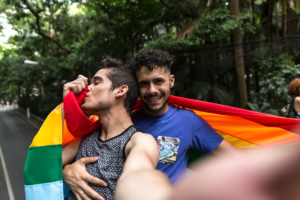 gay male couple embracing with the rainbow flag around their shoulders