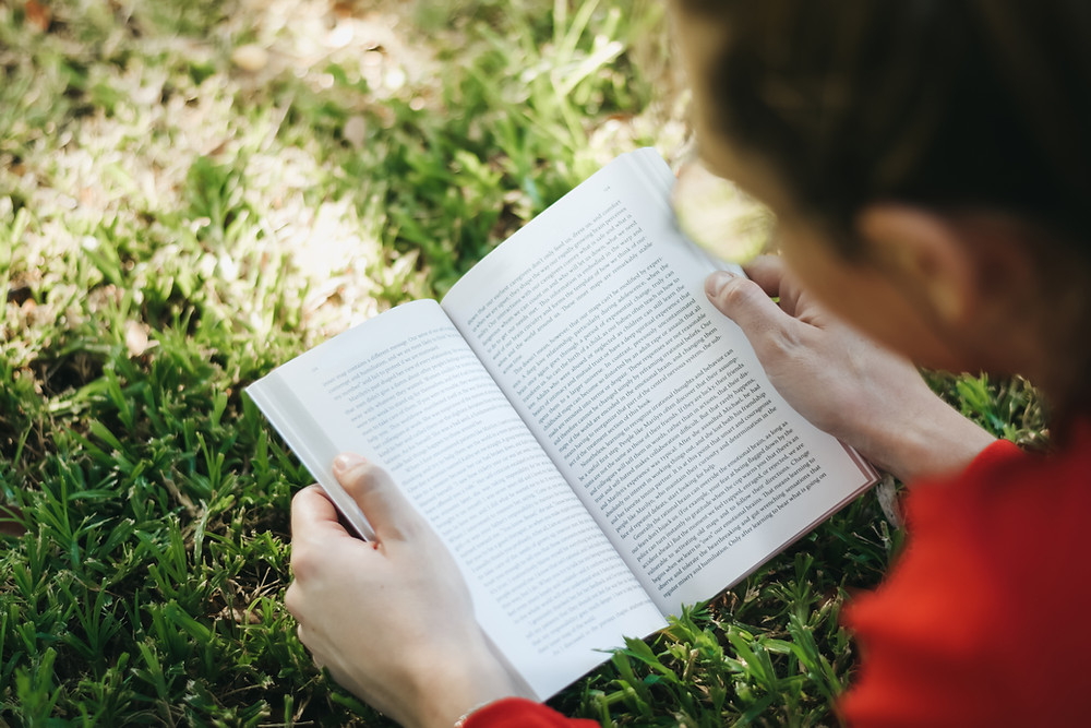 A woman reads a book outside, illustrating how she has overcome a difficulties in reading with The Key Clinic