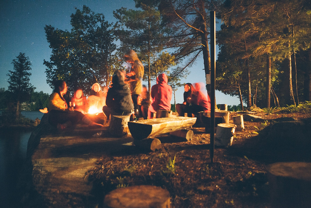 People crowded around a campfire at night.