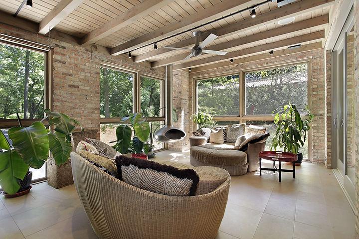 Terraza acristalada con muebles de mimbr