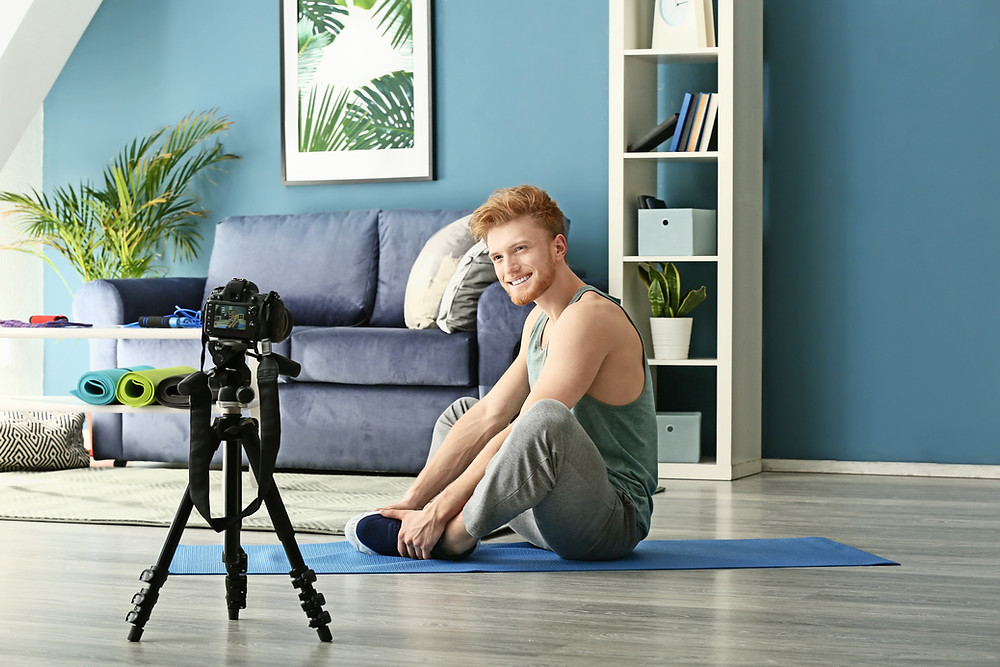 Man taking online fitness club in a blue room.