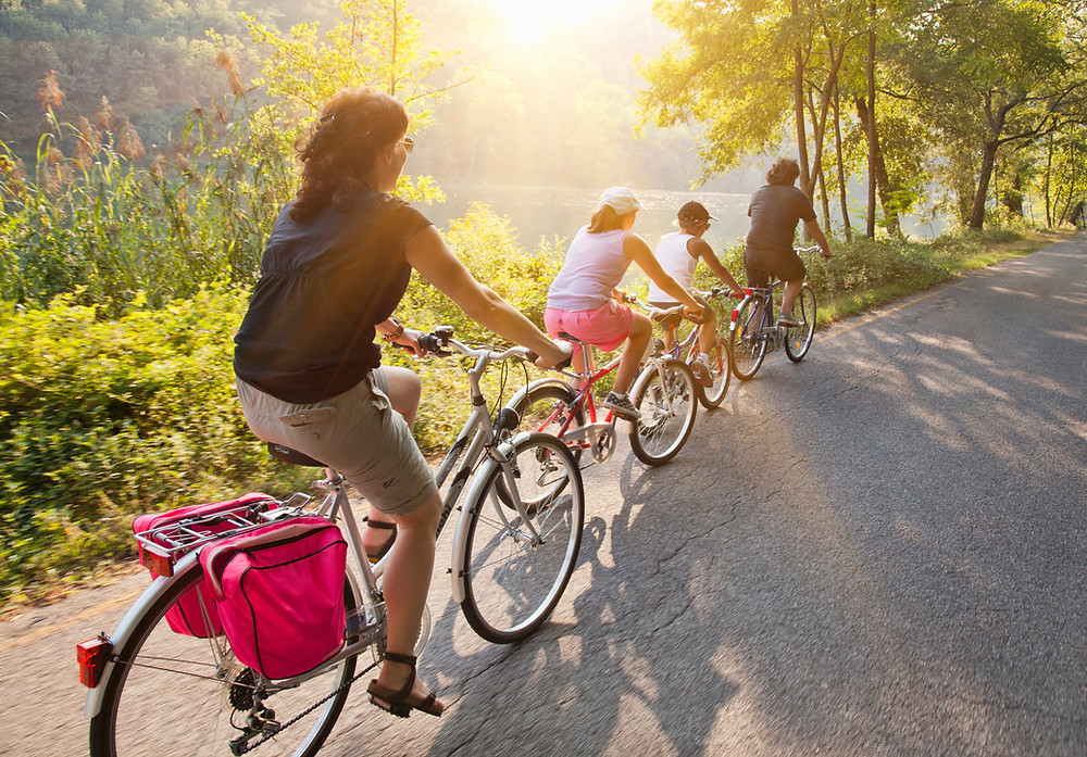 family bike riding on trail next to water fall scene