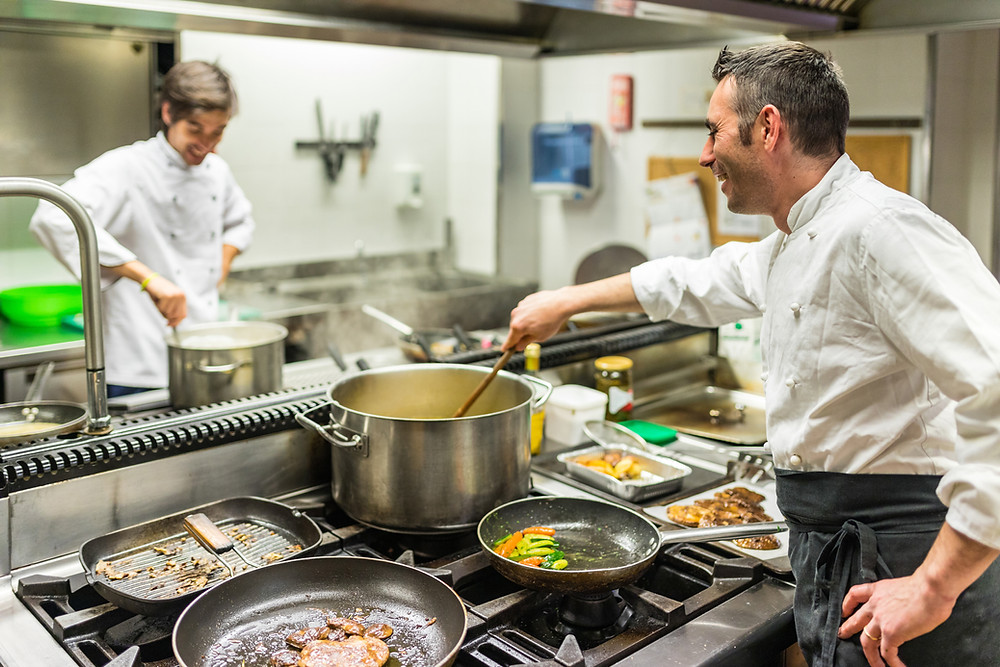 Chefs in a kitchen making soup in big pots