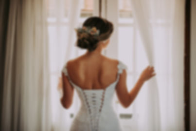 Rear view of a bride wearing an open back wedding dress, facing the window.