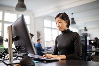 Asian young lady in black turtleneck is seated and facing a large computer screen, while her hands are both visibly resting on flat slanted keyboard. Open office area behind her, with oversized windows, white walls. One man in blue shirt seated in background, at computer screen and facing opposite direction