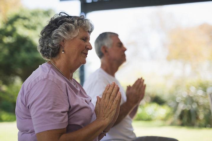 Couple de personnes âgées méditant