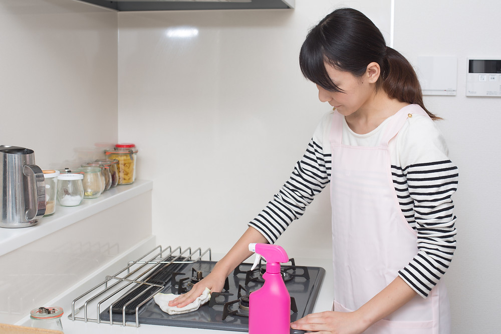 Woman wiping down her stove