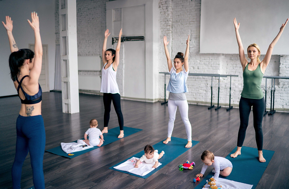 3 mums and there babies being taught by an instructor in a fitness class standing tall with their arms straight above their head.