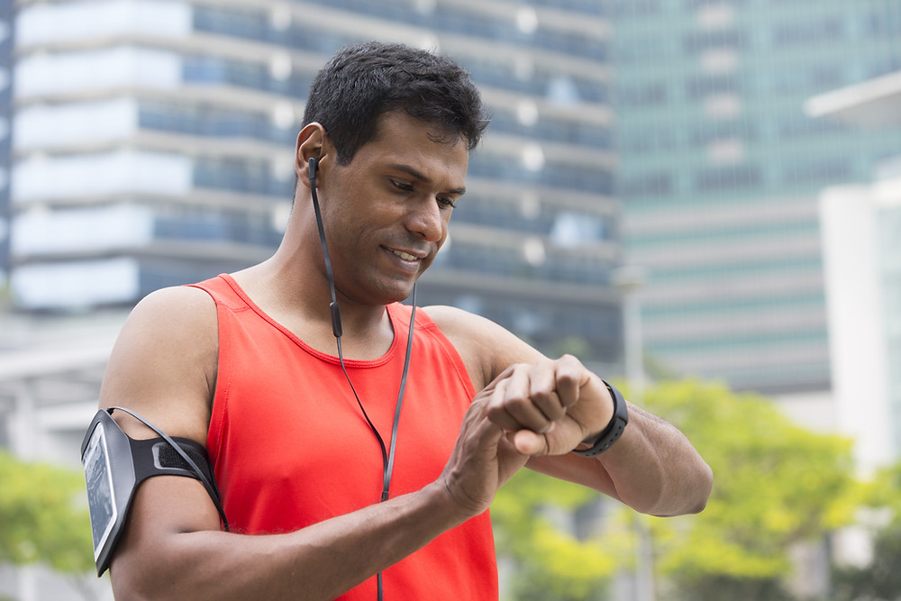 This is a picture of a man who is exercising. He's wearing an orange tank top, earbuds, an arm band with a cell phone, and a fitness tracker. He's looking at his fitness tracker.