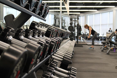 Modern gym with one person lifting dumbbells