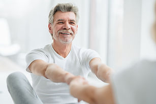 Older Man Smiling While Stretching | Angel Heart Home Care | The Best Care for Your Loved Ones
